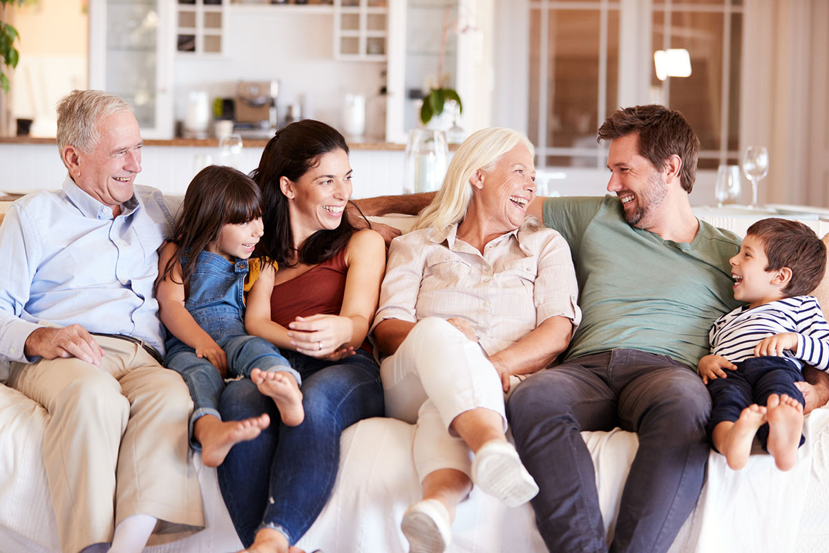 Happy three generation white family sitting on a sofa at home looking at each other, front view