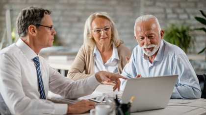Mature couple and insurance agent using computer during consultations in the office.